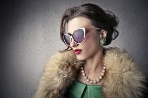 Photo of a glamorous woman wearing a fur stole and a necklace